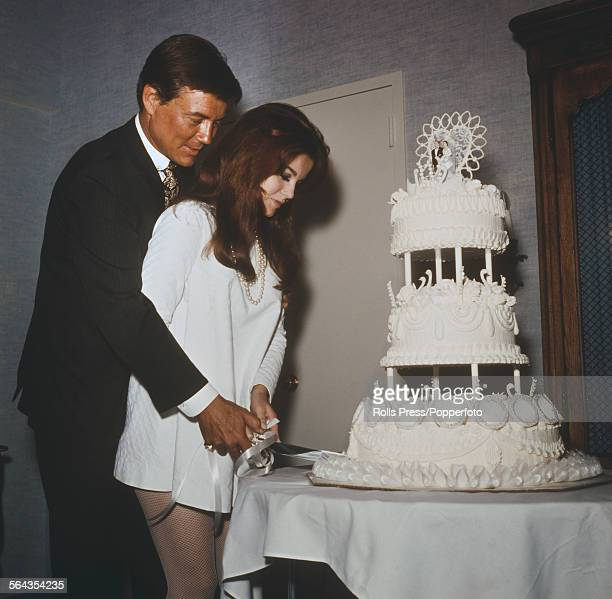 Swedish born American actress AnnMargret and her husband American actor Roger Smith cut their wedding cake after their wedding ceremony at the...