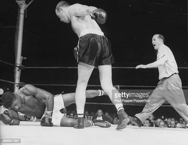 Swedish boxer Ingemar Johansson stands over his opponent Floyd Patterson during the 3rd round of their world heavyweight title fight watched by...