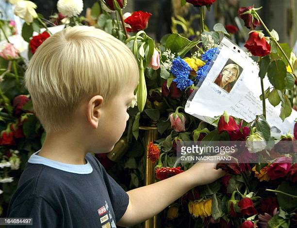 A Swedish boy touches the flowers outside the NK department store in Stockholm 18 September 2003 exactly a week after that Swedish Foreign Minister...
