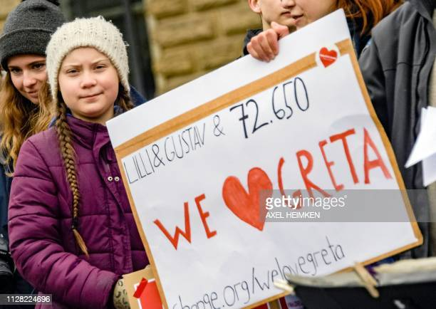 Swedish climate activist Greta Thunberg holds a placard bearing the number of signatures of a petition to support her during a demonstration of...