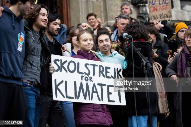 Swedish climate activist Greta Thunberg holds up a sign featuring the main slogan of her movement 'School strike for the climate' after speaking to...