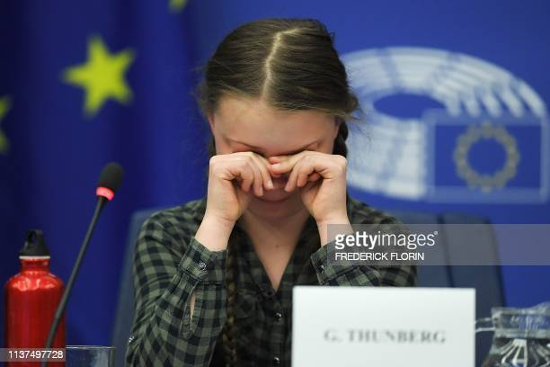 TOPSHOT Swedish climate activist Greta Thunberg reacts during a debate with the EU Environment Public Health and Food Safety Committee during a...