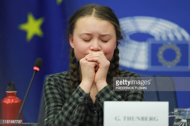 Swedish climate activist Greta Thunberg reacts during a debate with the EU Environment Public Health and Food Safety Committee during a session at...