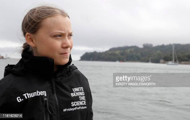 TOPSHOT Swedish climate activist Greta Thunberg walks along the quayside to board an electric powered rib before travelling to board the Malizia II...