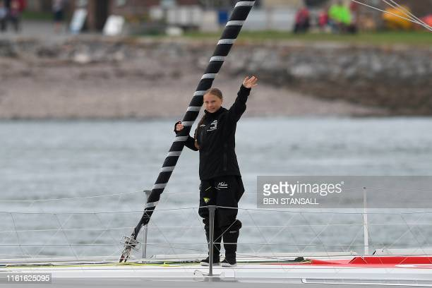 Swedish climate activist Greta Thunberg waves from aboard the Malizia II IMOCA class sailing yacht off the coast of Plymouth southwest England on...