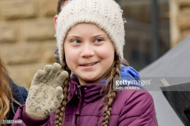 Swedish climate activist Greta Thunberg waves on stage during a demonstration of students calling for climate protection on March 1 2019 in front of...