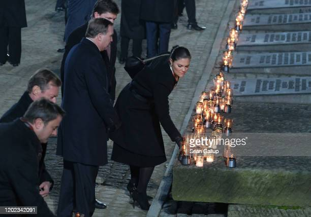 Swedish Crown Princess Victoria lays a candle at the Auschwitz Memorial as Swedish Prime Minister Stefan Löfven and her husband Prince Daniel look on...