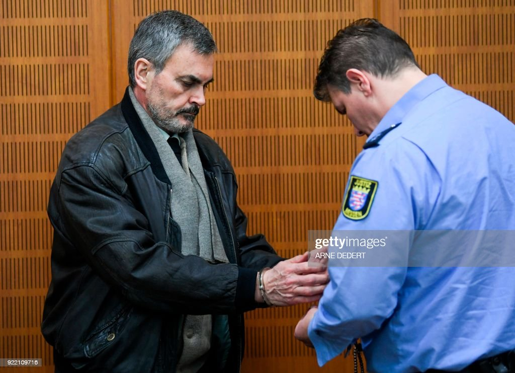 Swedish defendant John Ausonius, also know as 'Laser man', accused for the murder of 68-year-old Jewish Holocaust survivor Blanka Zmigrod in Frankfurt in 1992, gets his handcuffs off as he arrives for his trial in a courtroom at court in Frankfurt am Main, western Germany, on February 21, 2018. The court on February 21, 2018 jailed for life the convicted killer, dubbed 'the laser man' for using a laser-scoped rifle to target immigrants, for the murder of the Jewish woman. John Ausonius, 64, has already received a life prison term in Sweden for a six-month shooting spree in 1991-92 in which he killed or wounded 11 immigrants. PHOTO / dpa / Arne Dedert / Germany OUT