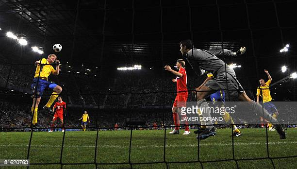 Swedish defender Petter Hansson L0 heads off the ball in front of teammate goalkeeper Andreas Isaksson during the Euro 2008 Championships Group D...