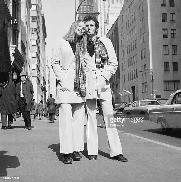 Swedish designer Sighten Harrgard and his fiancee Ann Jennifer model the designer's newest look for fall a unisex belted jacket and scarf with...