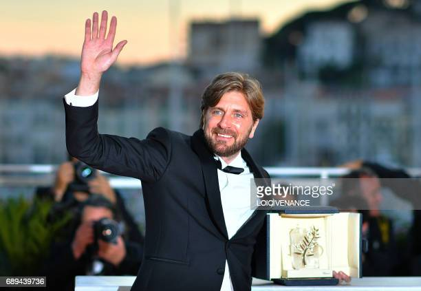 TOPSHOT Swedish director Ruben Ostlund celebrates with his trophy during a photocall on May 28 2017 after he won the Palme d'Or for his film 'The...