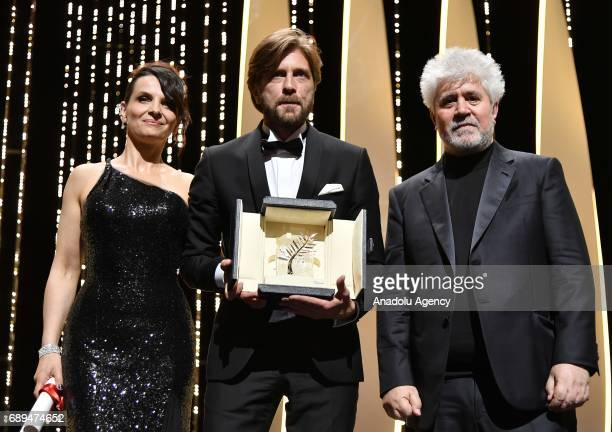 Swedish director Ruben Ostlund pose with President of the Jury Pedro Almodovar and French actress Juliette Binoche after he won the Palme d'Or Prize...