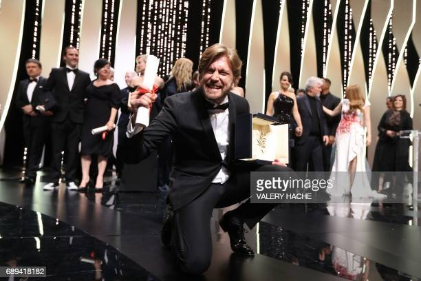 Swedish director Ruben Ostlund poses on stage with his trophy after he won the Palme d'Or for his film 'The Square' on May 28 2017 during the closing...