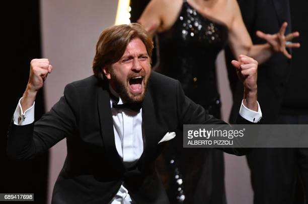 Swedish director Ruben Ostlund reacts on stage after he was awarded with the Palme d'Or for the film 'The Square' on May 28 2017 during the closing...