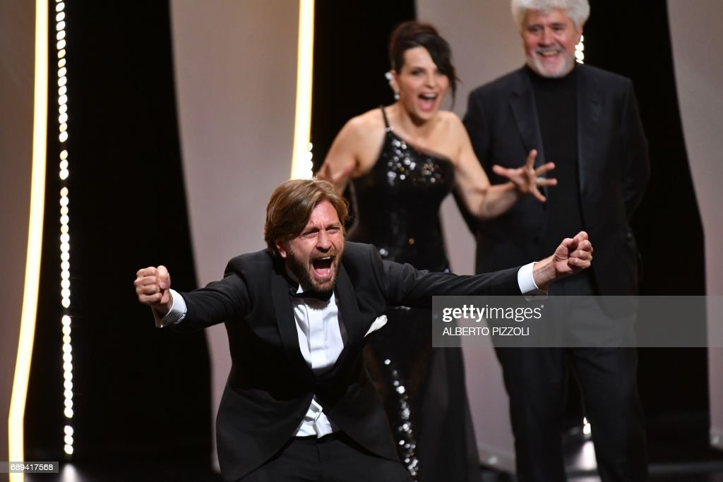Swedish director Ruben Ostlund reacts on stage as French actress Juliette Binoche (Rear C) and Spanish director and President of the Feature Film Jury Pedro Almodovar look on, after he was awarded with the Palme d'Or for the film 'The Square' on May 28, 2017 during the closing ceremony of the 70th edition of the Cannes Film Festival in Cannes, southern France. / AFP PHOTO / Alberto PIZZOLI