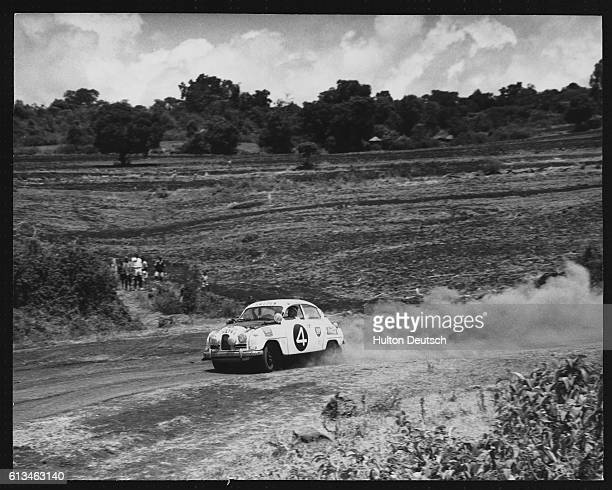 Swedish driver Eric Carlsson races his SAAB rally racecar during the 3100 mile East African Safari Rally The car eventually developed a collapsed...