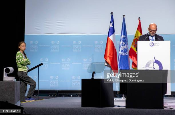 Swedish environment activist Greta Thunberg stands on the border of the stage as a speaker talks at the plenary session during the COP25 Climate...