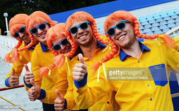Swedish fans dressed as the fictional character Pippi Longstocking cheer their national football players during a training session on June 13 2012 at...