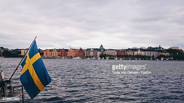 Swedish Flag By Lake Against Sky In City