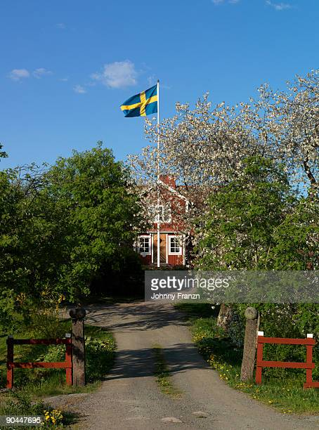Swedish flag in front of a red house Smaland Sweden.