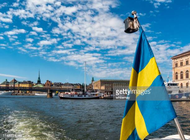 swedish flag with part of stockholm harbour, sweden - the stockholm palace stock pictures, royalty-free photos & images