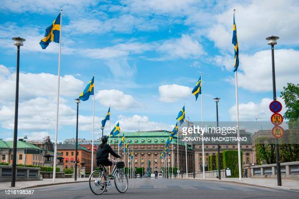 Swedish flags fly as a woman rides her bike in Stockholm on May 29 amid the coronavirus COVID-19 pandemic. - Sweden's two biggest opposition parties...