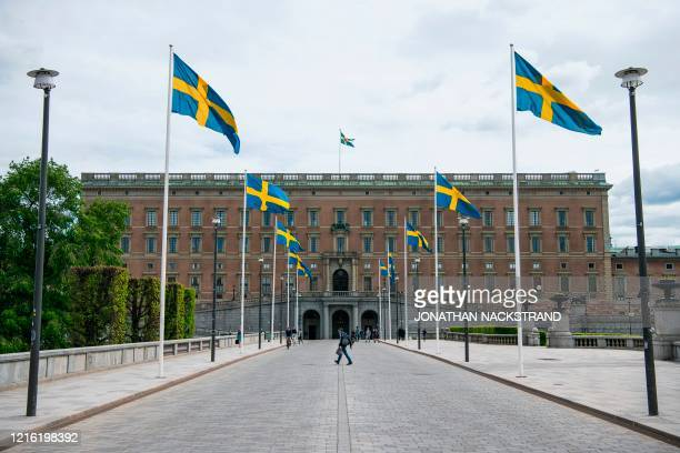 Swedish flags fly in front of the Royal Palace in Stockholm on May 29 amid the coronavirus COVID19 pandemic Sweden's two biggest opposition parties...