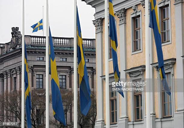 Swedish flags outside the Foreign Ministry and on top of the Riksdag the parliament building in Stockholm are lowered to half mast 01 January 2004 as...