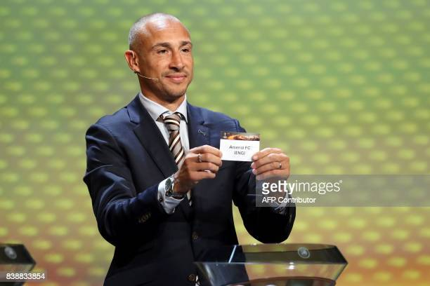 Swedish football coach Henrik Larsson shows the sheet of paper bearing the name of the Arsenal FC football team as he proceeds to the draw for the...