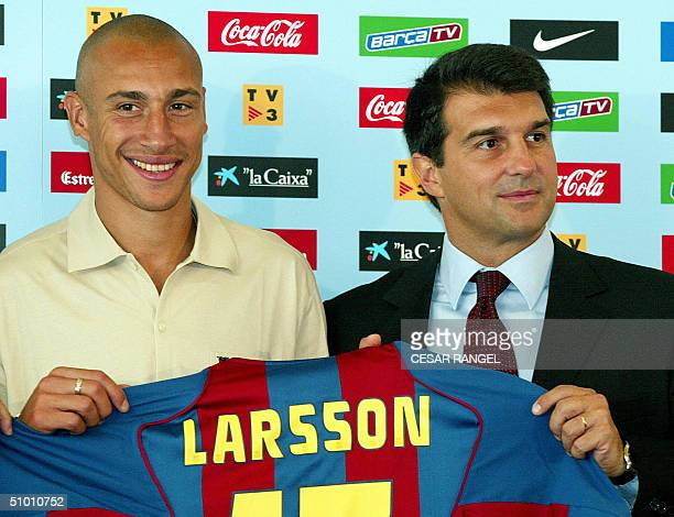 Swedish football player Henrik Larsson shows off his new Barcelona club jersey next to Barcelona's club president Joan Laporta during his official...
