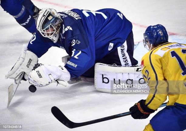 Swedish forward Joel Kellman attacks Finnish goalkeeper Ramas Tirronen during the Channel One Cup of the Euro Hockey Tour ice hockey match between...