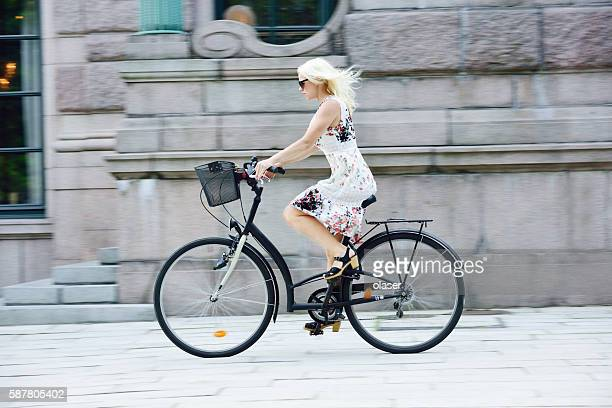 Swedish girl in summer dress on bicycle in city