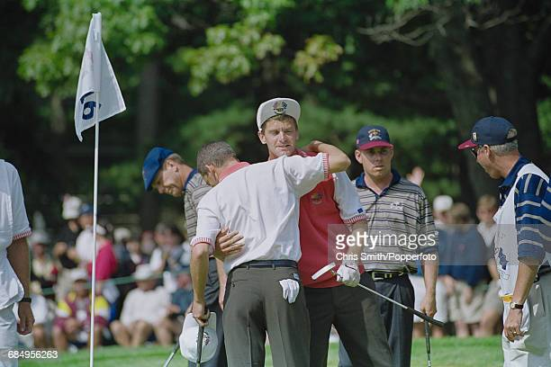 Swedish golfer Jesper Parnevik pictured centre embraces his playing partner Spanish golfer Sergio Garcia after gaining points in action for Team...