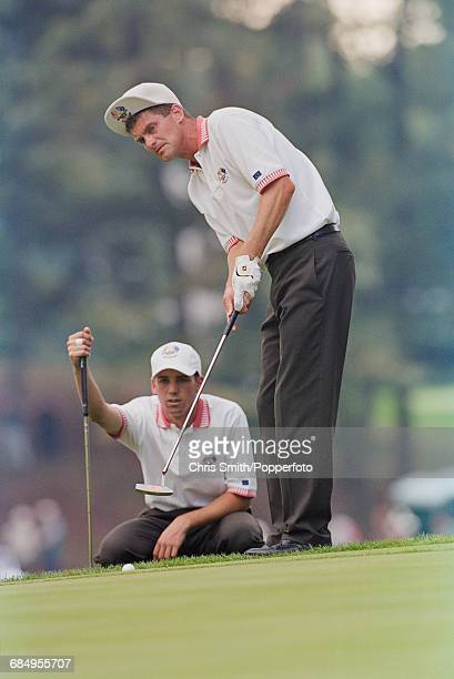 Swedish golfer Jesper Parnevik plays a putt on a green as his playing partner Spanish golfer Sergio Garcia observes from behind during action for...
