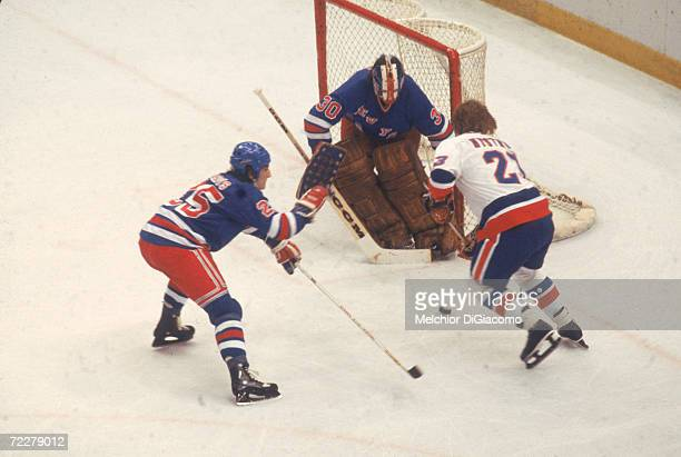 Swedish hockey player Bob Nystrom of the New York Islanders tries to slip the puck past Canadian hockey player John Davidson goalkeeper for the New...