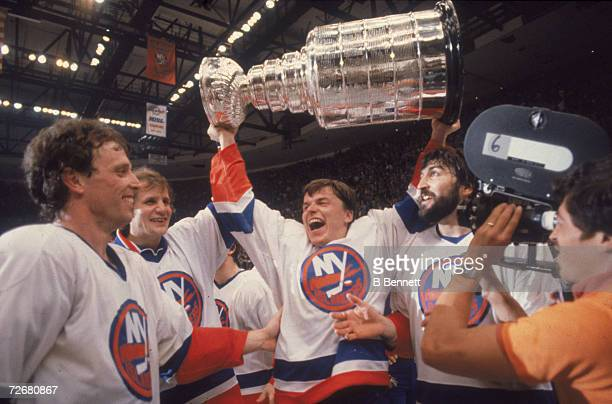 Swedish ice hockey player Anders Kallur of the New York Islanders raises the Stanley Cup aloft as he celebrates victory with teammates, from left,...