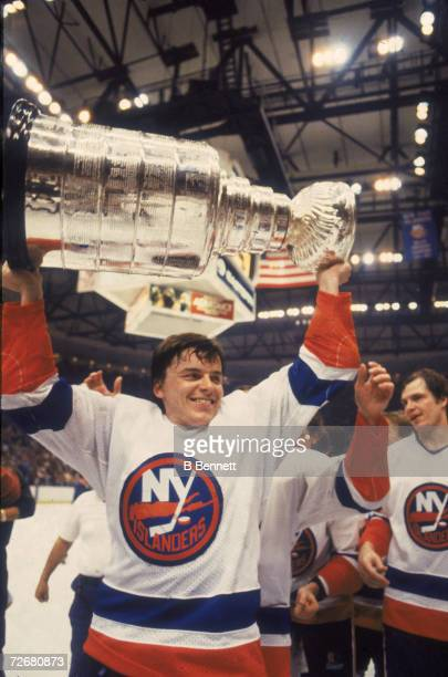 Swedish ice hockey player Anders Kallur of the New York Islanders celebrates his team's fourth consecutive Stanley Cup victory by raising the cup...