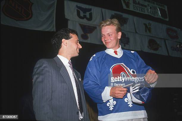 Swedish ice hockey player Mats Sundin wears a Quebec Nordiques jersey as he smiles at an unidentified man following his first round, first place...