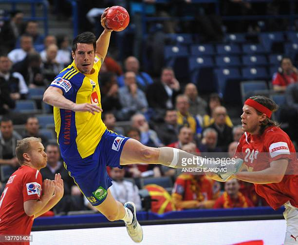 Swedish Kim Andersson shoots the ball past Danish Anders Eggert Jensen and Mikkel Hansen during their Men's EHF Euro 2012 Handball Championship match...