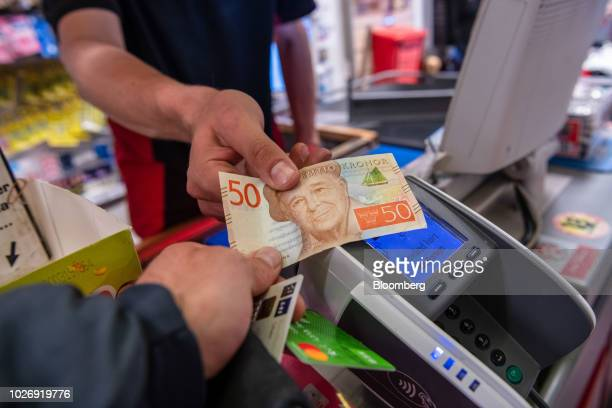 Swedish kronor note is handed over at a grocery store, near a card payment terminal, in this arranged photograph in Stockholm, Sweden, on Tuesday,...