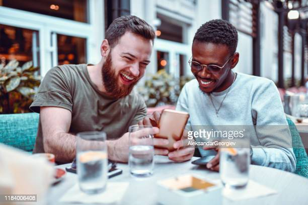 swedish male laughing while browsing social media with his african friend - facebook friends stock pictures, royalty-free photos & images
