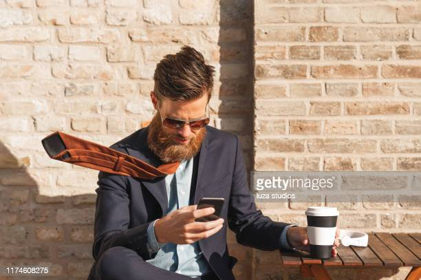 a swedish man is using his smart phone on a coffee break in the city - wind stock pictures, royalty-free photos & images