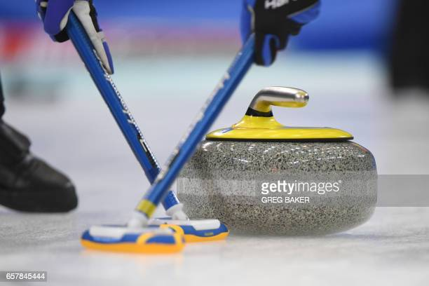 Swedish players sweep ahead of the stone during the bronze medal match against Scotland at the Women's Curling World Championships in Beijing on...
