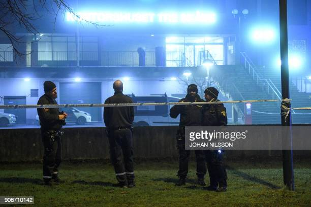 Swedish police officers stand guard within a security perimeter set around an office building after an explosion on January 21 2018 in the Rosengard...