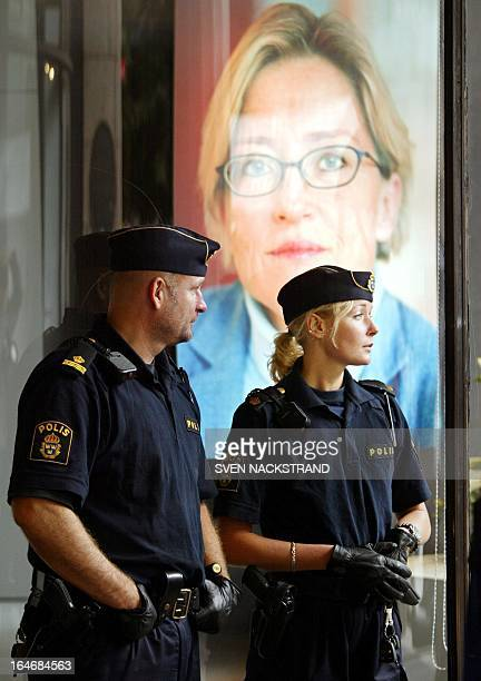 Swedish police stand on guard by a poster of Foreign Minister Anna Lindh displayed next to the mountain of flowers in her memory outside the NK...