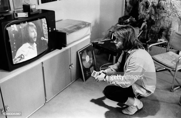 Swedish Pop musician Benny Andersson, of the group ABBA, crouches down as he watches himself perform on televsion in Polar Studios, which he...