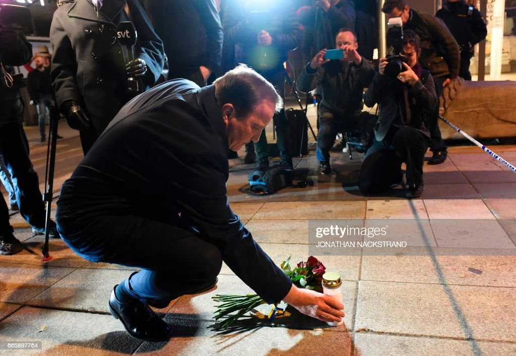 TOPSHOT - Swedish Prime Minister Stefan Lofven lays flowers and a candle at the scene where a truck slammed into a crowd of people outside a busy department store in central Stockholm, causing 'deaths' in what the prime minister described as a 'terror attack' on April 7, 2017. / AFP PHOTO / Jonathan NACKSTRAND