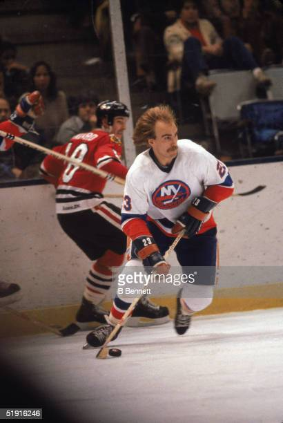 Swedish professional hockey player Bob Nystrom forward of the New York Islanders skates by Canadian hockey player Denis Savard forward of the Chicago...