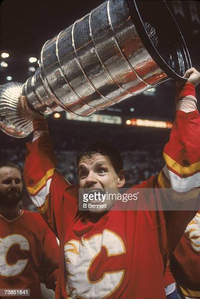 Swedish professional ice hockey player Hakan Loob Calgary Flames hoists the Stanley Cup trophy over his head in celebration of his team's defeat of...