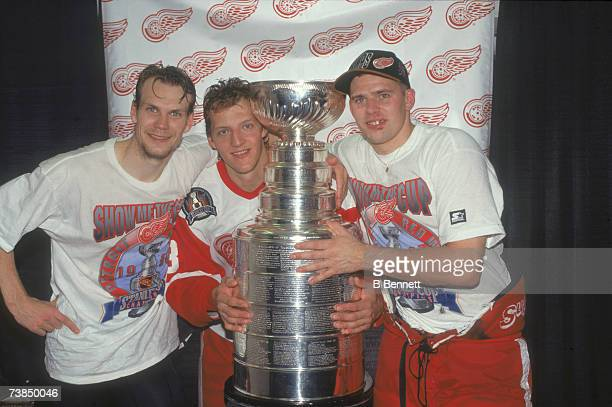Swedish professional ice hockey players Nicklas Lidstrom Tomas Sandstrom and Tomas Holmstrom pose with the Stanley Cup trophy after their team's...
